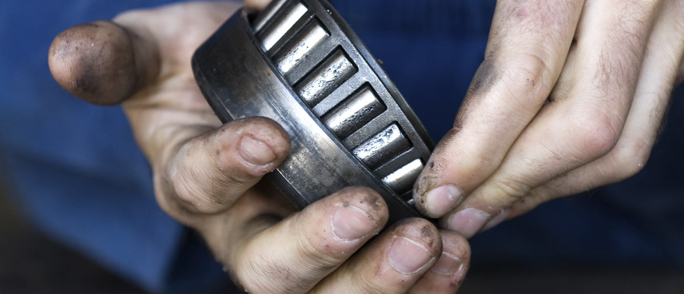 man's hands holding metal part for machine repair